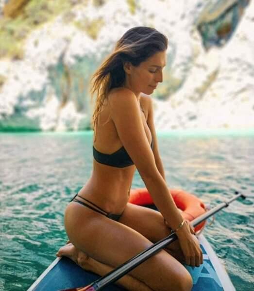 Après une session de paddle, Laury Thilleman prend la pose sur sa planche dans son joli deux-pièces