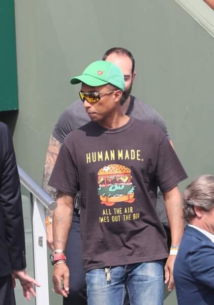 Pharrell Williams avec une casquette verte pour se protéger du soleil
