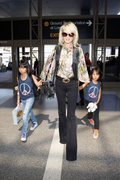 Laeticia Hallyday en blouse imprimée, sac à franges et pantalon bootcut, avec Jade et Joy à Los Angeles en 2015