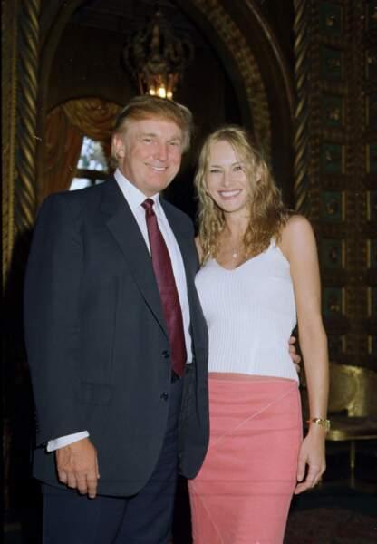 Melania, alors blonde, avec son futur époux Donald Trump à Mar-a-Lago en Floride, le 23 avril 2000. Elle arborait un look simple, en rose et blanc.