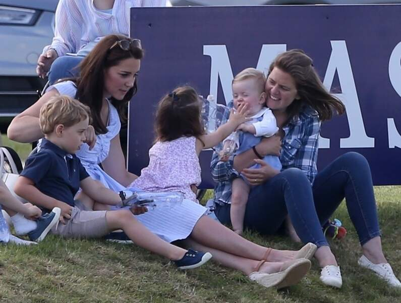 La princesse Charlotte mettant une main sur la bouche du bébé en face d'elle
