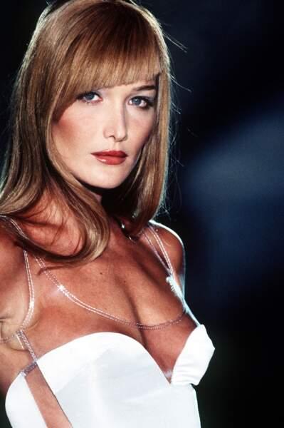 Carla Bruni, chevelure blond foncé et frange asymétrique, sur le défilé Versace en 1995 à Paris