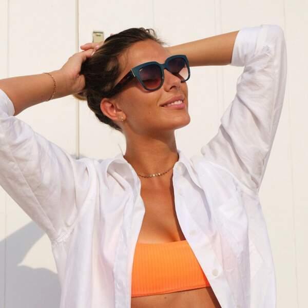Un top bandeau orange porté sous une chemise blanche : un look estival pétillant pour Camille Cerf