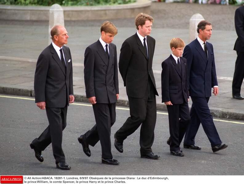 Le jeune Harry, entre son père et son oncle, Charles Spencer. Dévasté, il  serre les poings pour ne pas pleurer