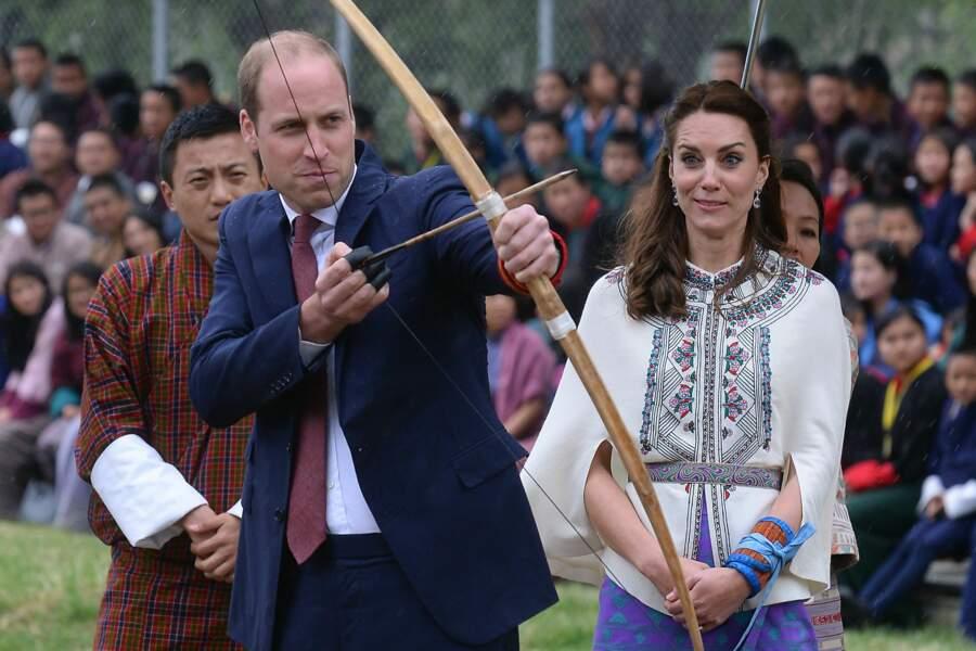 Le prince William concentré avant de tirer sa flèche, devant l'oeil inquiet de son épouse