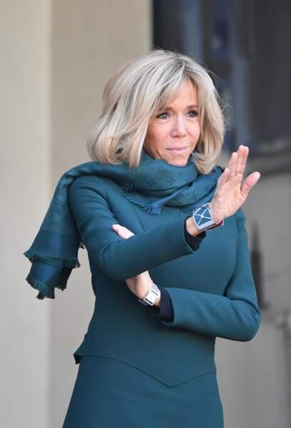 En total look vert, Brigitte Macron assortit son écharpe et son bracelet à sa robe courte
