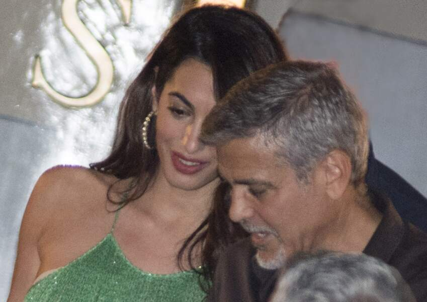 Amal Clooney, cheveux lâchés, créoles et robe longue verte Stella Mac Cartney