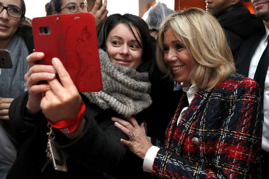 Brigitte Macron très souriante pose avec une fan à l'hôpital de Saint-Denis