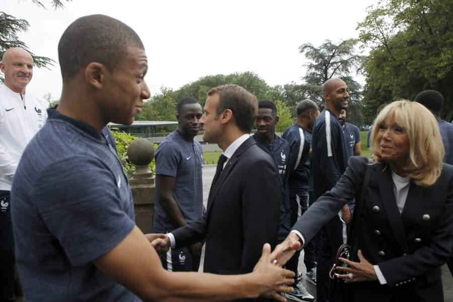 Brigitte Macron en blazer et jean slim serre la main de Kilian Mbappé