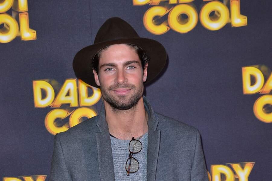 Tom Leeb, chapeau vissé sur la tête et lunettes accrochées à son pull