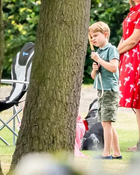 Le prince George mettant la cross de polo de son père sur son visage en juillet 2019