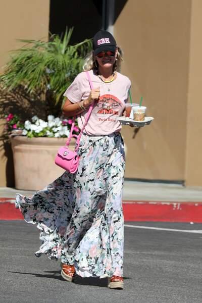 Laeticia Hallyday mixe t-shirt rose pâle avec une jupe volantée et un sac flashy.