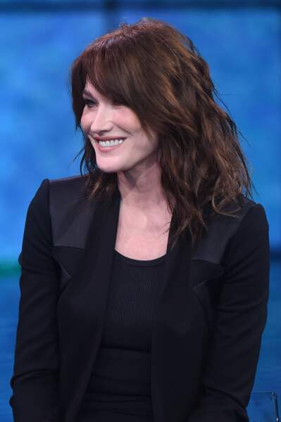 Carla Bruni et ses cheveux ondulés châtain foncé, sur le plateau d'une émission en Italie, le le 3 février 2018