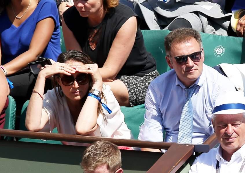 Le soleil tape et la compagne de Pierre Sled se concentre attentivement sur le match à Roland Garros