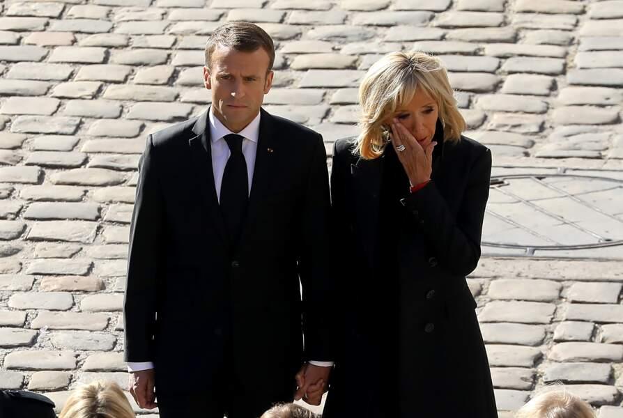 Brigitte Macron essuie une larme sur sa joue lors de l'hommage national à Charles Aznavour