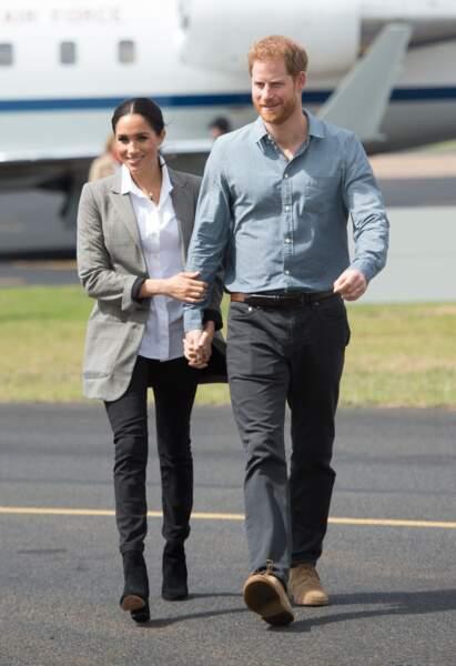 Meghan Markle, enceinte, opte pour un jean noir slim à son arrivée en Australie pour une tenue relax et chic.