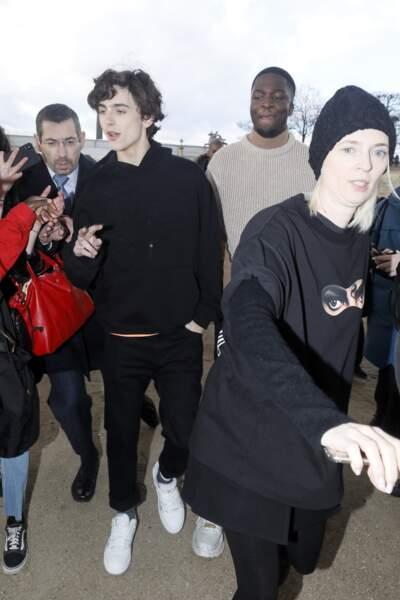 Pull à capuche noir, jeans et baskets signent le look de Timothée Chalamet pour le show Louis Vuitton homme.