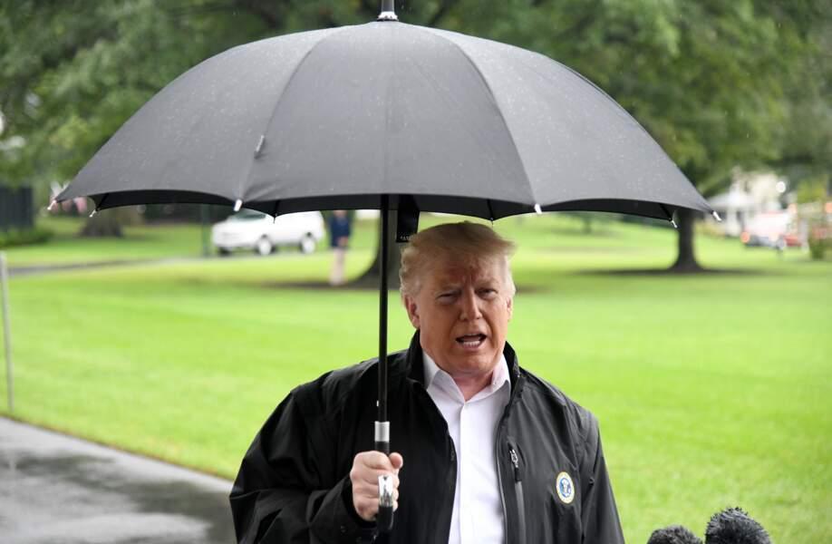 Donald Trump sous son parapluie parlant à des journalistes près de la Maison Blanche