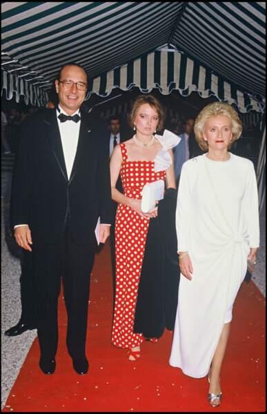 Bernadette, en longue robe drapée blanche, avec Jacques et Claude Chirac lors d'une soirée à Paris en 1985