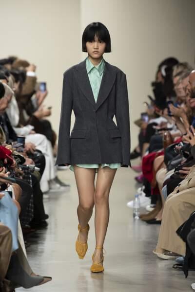 Gauchere ajuste la veste de blazer, comme une robe, ultra féminine.