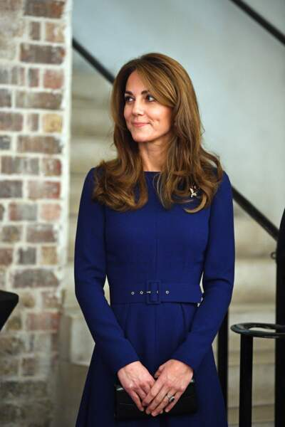 Kate Middleton en robe bleue nuit ceinturée Emilia Wickstead, minaudière Aspinal of London et des escarpins Jimmy Choo