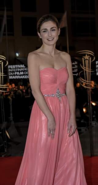 2012 : Julie Gayet a les cheveux longs, châtains foncés et relevés en chignon. Un look classe, qu'elle associe avec une robe rose à Marrakech.