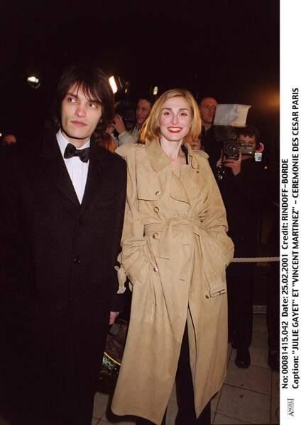 2001 : Julie Gayet adopte une coupe simple dans un blond doré qui va parfaitement avec son trench. Elle est accompagnée de Vincent Martinez.