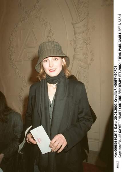 2002 : Julie Gayet a les cheveux mi-longs dans un blond/roux. Elle porte un bob kaki pour le défilé haute couture printemps/été de Jean-Paul Gaultier.