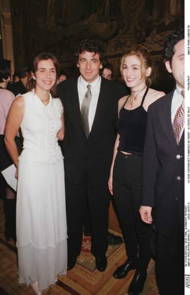1996 : Julie Gayet, cheveux relevés de couleur cuivre. La photo est prise aux côtés de Patrick Bruel pour la première édition du Festival des lumières.
