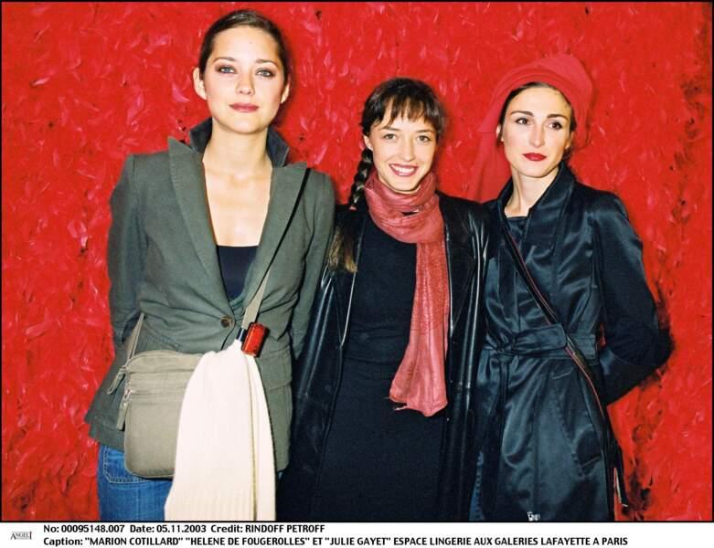 2003 : Julie Gayet a les cheveux châtains et porte un foulard rouge sur les cheveux. Elle est avec Marion Cotillard et Hélène de Fougerolles aux Galeries Lafayette.