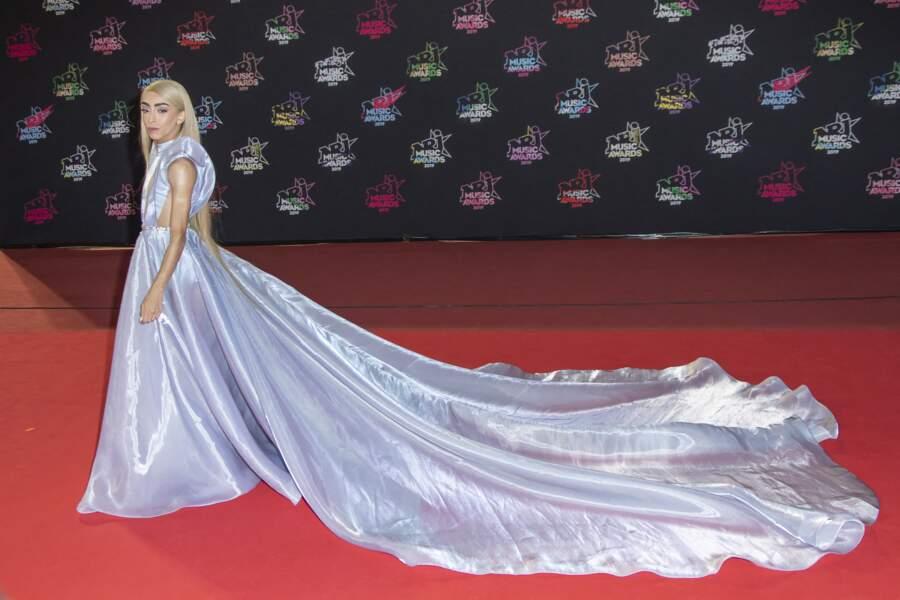 Bilal Hassani fait sensation avec une robe à la longue traîne aux reflets bleus et mauves, rappelant celle de Cendrillon