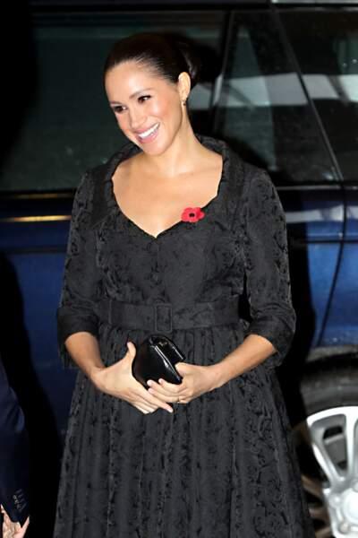 Cheveux tirés et noués en chignon, robe noire décolletée Erdem, Meghan Markle très chic le 9 novembre 2019