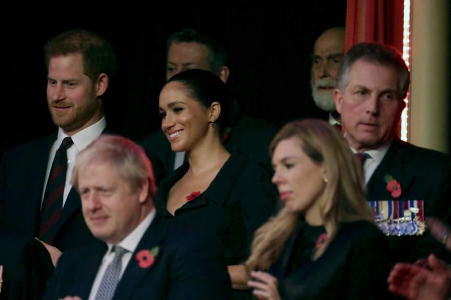 Tout sourire, Meghan Markle en robe noire décolletée signée du créateur britannique d'origine turque Erdem