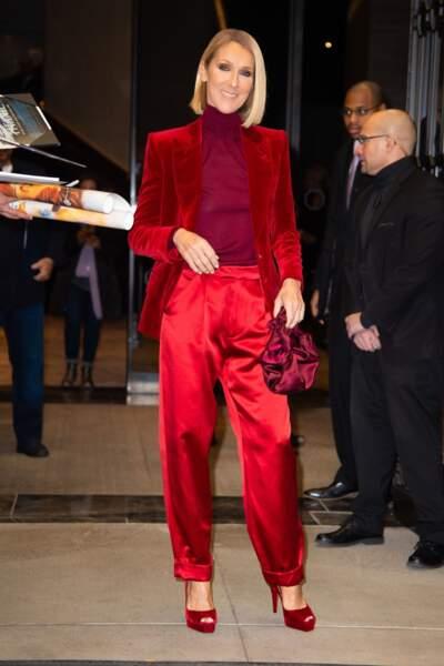 Céline Dion d'une élégance extrême dans cet ensemble mixant différentes nuances de rouge, mais joue aussi sur les matières entre la veste en velours et le pantalon satiné.
