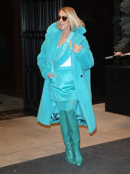 Céline Dion ose le mix manteau long, jupe courte, banane et cuissardes, dans une camaïeu de bleu ciel et bleu canard, le tout signé Max Mara.