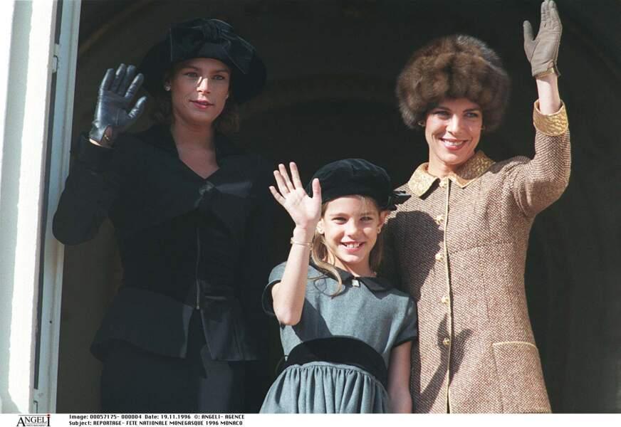 1996 : Charlotte Casiraghi tout sourire et entourée de Caroline et Stéfanie de Monaco. Elles saluent la foule ensemble.