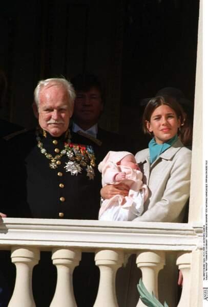 1999 : Charlotte Casiraghi est aux côtés du Prince Rainier et tient sa sœur Alexandra de Hanovre dans ses bras lors de son apparition au balcon.