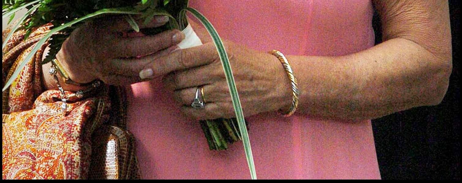 Zoom sur la bague de fiançailles de Camilla Parker Bowles. Montée sur platine, le bijoux est orné d'un diamant central taillé en coussin, tandis que trois autres diamants sertissent les côtés.