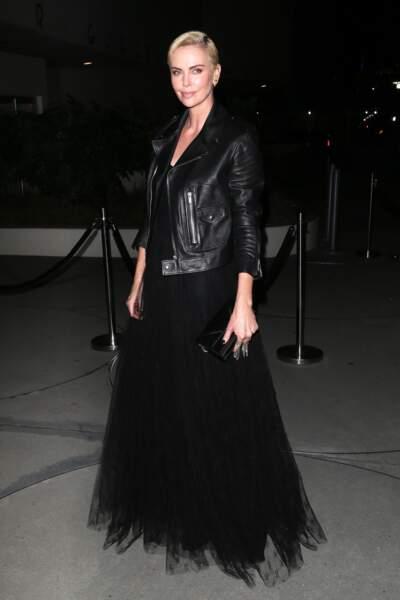 Charline Theron porte une veste en cuir au-dessus de a longue robe noire en tulle.
