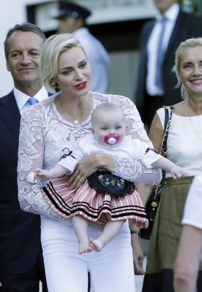 28 août 2015 : La princesse Charlène tient sa fille Gabriella dans ses bras. La petite est habillée en costume traditionnel à l'occasion du pique-nique de la Principauté au parc Antoinette. La princesse âgée de quelques mois, décroche un sourire vraiment mignon pour la photo.