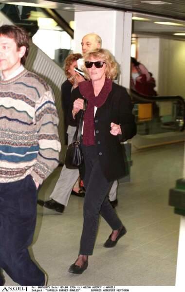 """Avril 1996 : Camilla Parker Bowles est habillée """"décontracté"""" pour se rendre à l'aéroport Heathrow. Jean, gilet, chaussures plates et lunette de star, Camilla porte un look au goût du jour."""