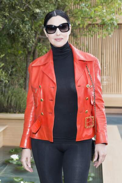 Monica Belluci au top du glamour dans un total look noir rehaussé par une veste perfecto rouge flashy griffée Chanel.