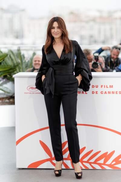 Monica Bellucci glamour dans une combinaison noire marquée à la taille par une ceinture extra-large en satin.