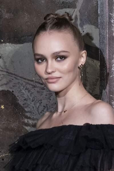 Les cheveux plaqués en chignon, Lily-Rose Depp a opté pour une mise en beauté discrète avec de grandes créoles