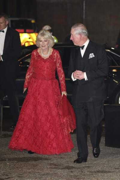 6 décembre 2016 : Lors du Royal Variety Performance, Camilla Parker Bowles, accompagnée de son époux, le prince Charles, ose le rouge avec une robe longue en dentelle. Elle porte tout de même le traditionnel collier de perles.