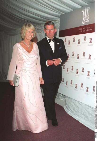 21 juin 2000 : Camilla Parker Bowles aux côtés de son compagnon, le Prince Charles. Elle porte une robe rose satiné pour se rendre à un diner de la fondation des Princes.
