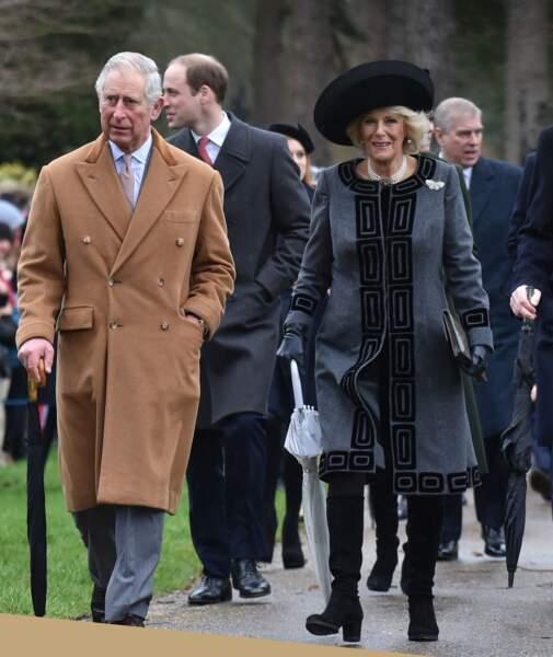 25 décembre 2015 : Le prince Charles et la duchesse de Cornouailles à la sortie de la messe de Noël. Un tenue noir et grise avec un col montant jusqu'au cou, elle porte également son fameux collier de perles.