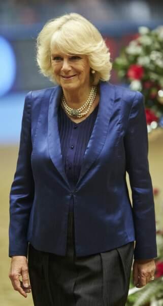 19 décembre 2013 : Lors d'un spectacle équestre en 2013 la duchesse de Cornouailles portait une veste de tailleur mais brillante cette fois-ci, et son collier de perles trois rangs.