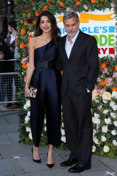 Amal Clooney canon dans une combinaison satinée asymétrique au bras de son époux George Clooney.
