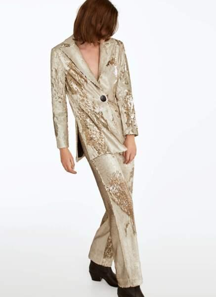La veste de costume à paillettes dorées assortie à son pantalon droit légèrement évasé dans le bas, 199€ et 125€, Uterquë.